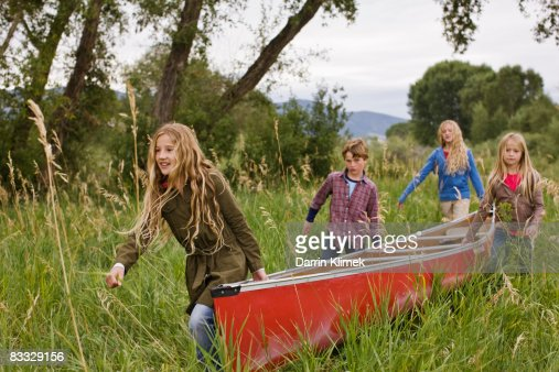 Kids carrying canoe through tall grass
