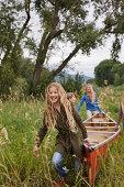 Kids carrying canoe through tall grass