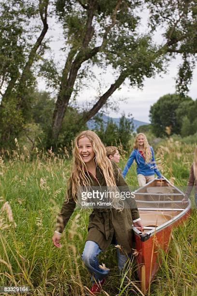 Les enfants portant canoë au Grande plante herbacée