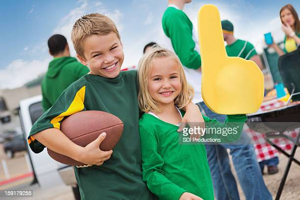 Kids cheering sports team during college football stadium tailgate party
