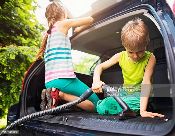 Kids cleaning family car interior