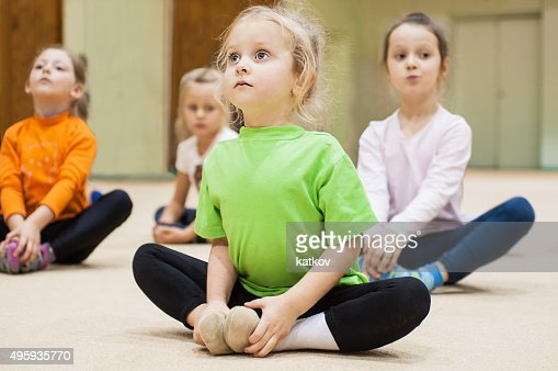 Kids doing exercise in gym : Stock Photo