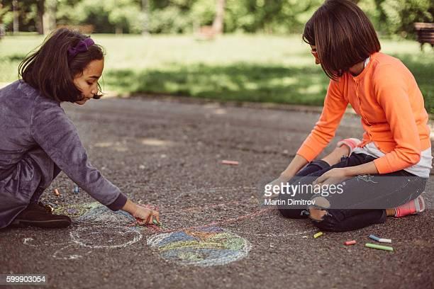 Enfants, dessin à la craie sur l'asphalte