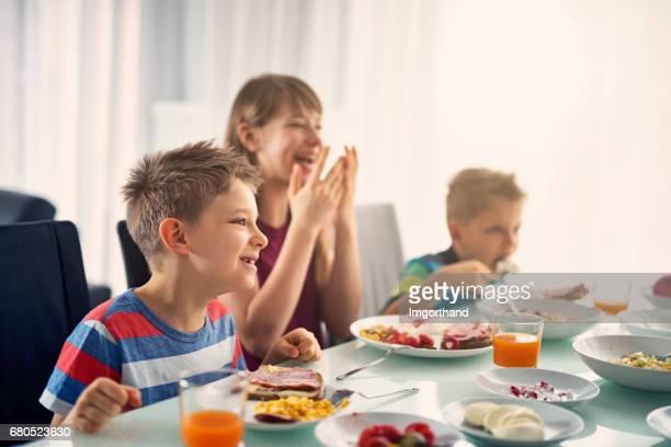 Kids eating breakfast on sunny morning