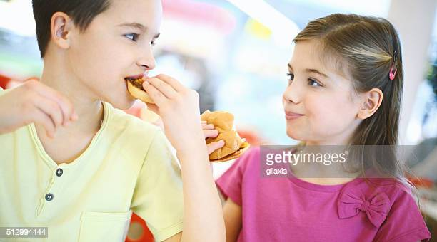 Kids eating burgers and talking.