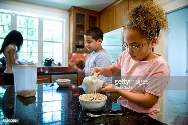 Niños comía cereal en la cocina