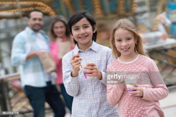 Kids eating ice cream at a fun fair with their parents