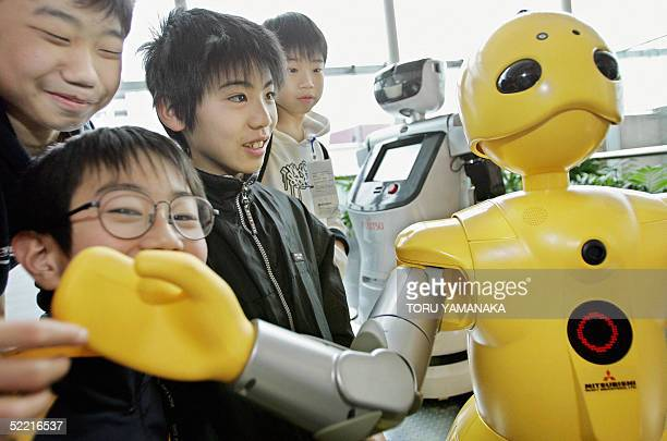 Kids enjoy listening to weather information from 'wakamaru' a humanoid robot of Mitsubishi Heavy Industries during an exhibition at the National...