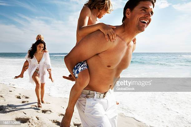 Kids enjoying piggy back rides on parents at the beach