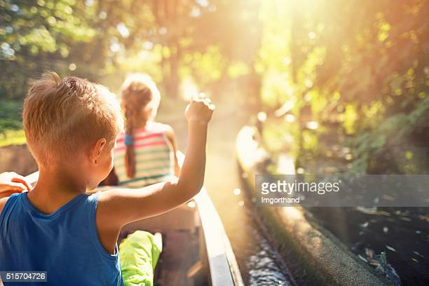Kids enjoying ride in a boat through the forest river