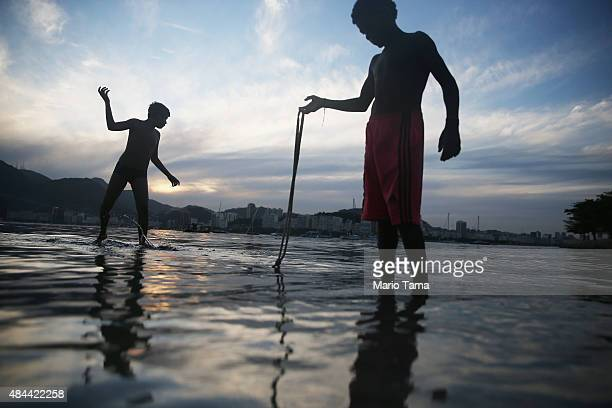 Kids fish in the polluted Guanabara Bay the Rio 2016 Olympic Games sailing venue on August 18 2015 in Rio de Janeiro Brazil Controversy has erupted...