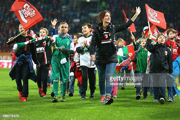 Kids from Bremen and Augsburg walk together on the field of play pror to the Bundesliga match between FC Augsburg and SV Werder Bremen at WWK Arena...