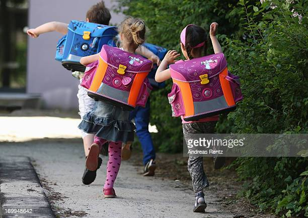 Kids from kindergarten 'Schneckenhaus' walk along a path with their new satchels on June 5 2013 in Berlin Germany