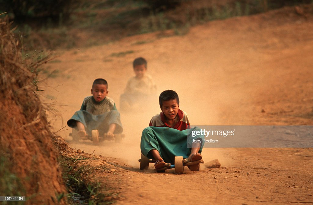 Kids from the Lisu hilltribe use hand-built wooden gocarts to race down the dirt roads cutting through a oolong tea plantation in rural Chiang Rai province..
