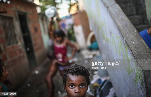 Kids gather and bathe from water gathered from one of the two community hoselines in an impoverished section of the Mare 'favela' community on...