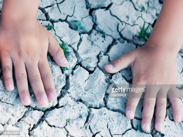 Kids hands on cracked drought soil