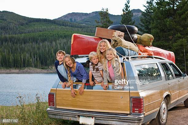 Kids hanging out of back of station wagon