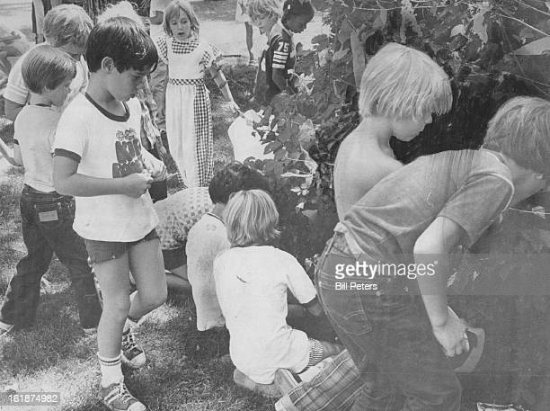 JUL 22 1975 JUL 30 1975 Kids have a hot time with christmas in July A city park bush makes a handy 'Christmas' tree when decorated with popcorn...
