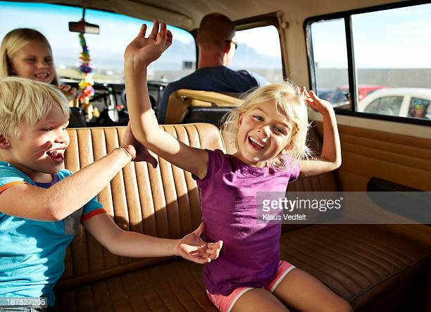 Kids having fun in back of old car