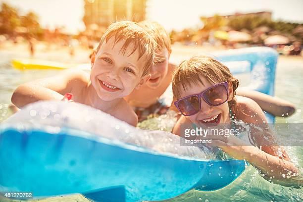 Kinder, die Spaß im Meer auf Luft Bett