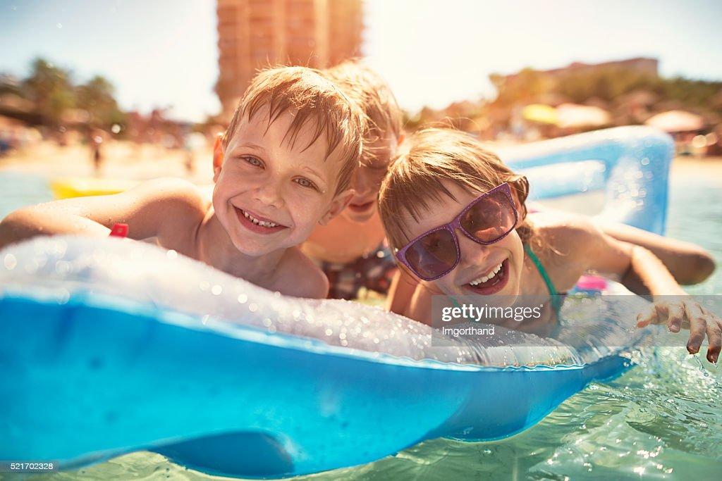 Ragazzi che si diverte nel mare in aria letto : Foto stock