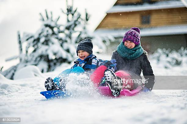 Kids having fun  in winter sliding on snow with sleds
