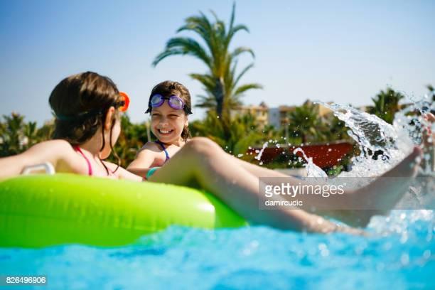 Kids having fun on innertubes in swimming pool