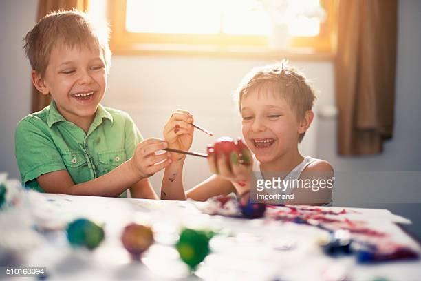 Crianças pintando ovos de Páscoa a divertir-se