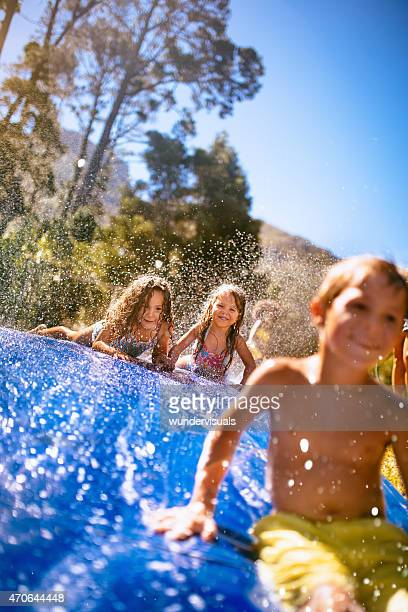 Kids having fun sliding down a slippery water slide