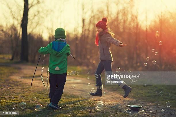 Enfants s'amuser avec des bulles sur le début du printemps