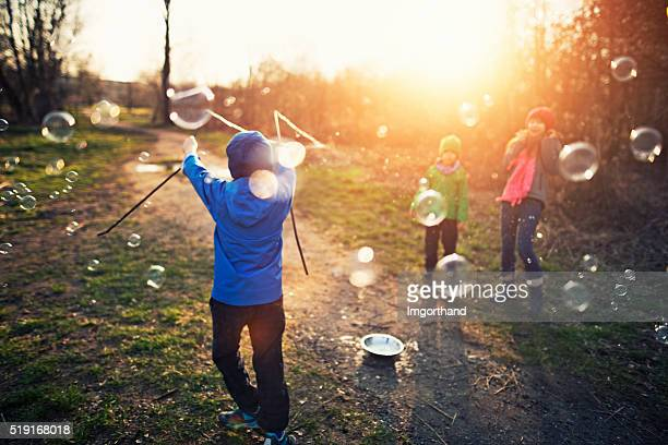 Kids having fun with bubbles on early spring