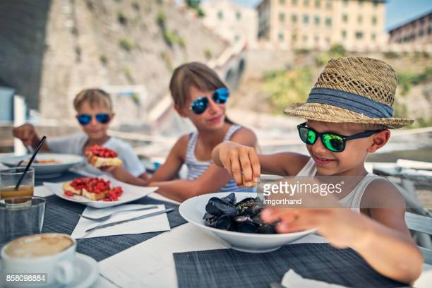 Kids having meal in italian restaurant