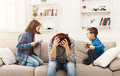 Kids having quarrel over tired mother. Mom is depressed by screaming of children. Problems of motherhood, copy space
