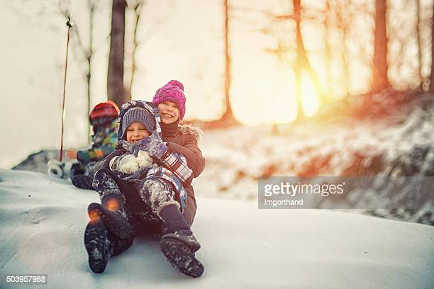 Kids having winter fun sliding on snow
