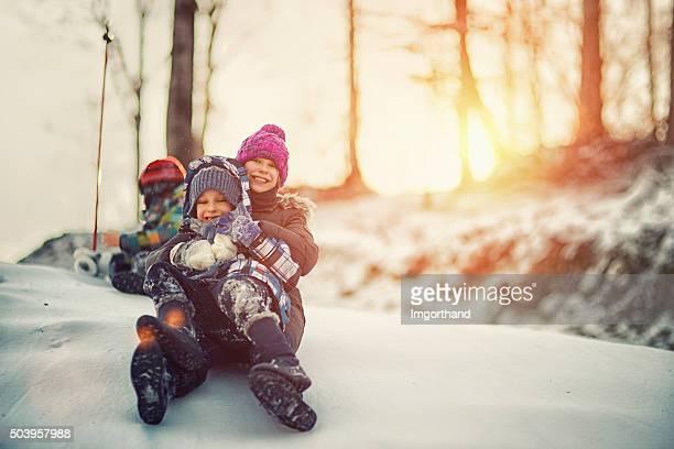 Kinder, die Spaß im winter auf Schnee Rutschen