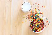 Kids healthy quick breakfast. Colorful rice cereal with milk on wooden background. Copy space