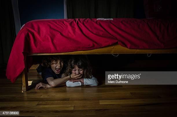 Enfants dissimulée sous le lit et la peur ou Pleurer