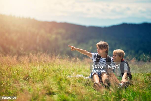 Kids hikers checking map on tablet in the grassy meadow