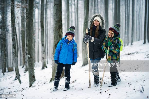 Kids hiking in misty winter forest