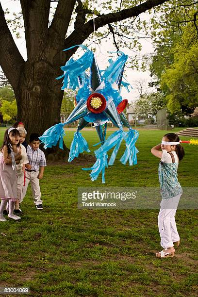 Kids hitting pinata in park