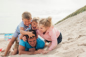 Children having fun at the beach with their father. Pining him down and tickling him.