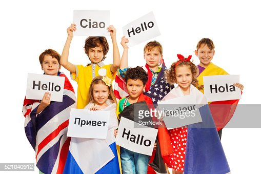 Kids holding greeting signs in different languages : Stock Photo