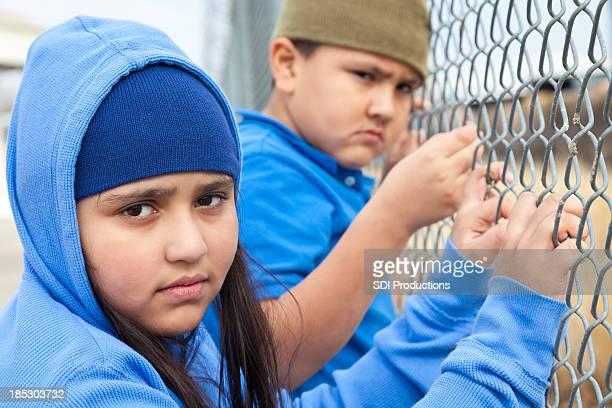 Kids holding onto fence