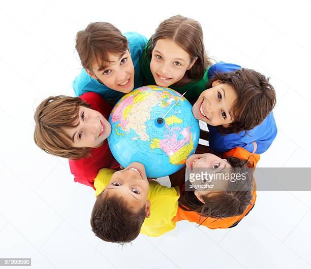 Kids holding together a terrestrial globe.