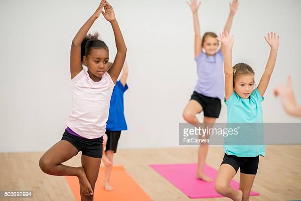 Kinder hält Baum Post in Yoga-Klasse