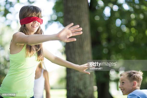 Kids in garden playing blind mans buff