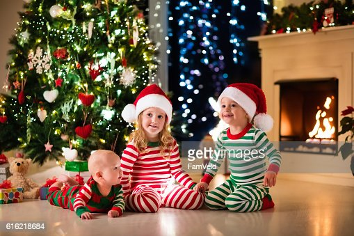 Kids in pajamas sitting under Christmas tree : Stock Photo