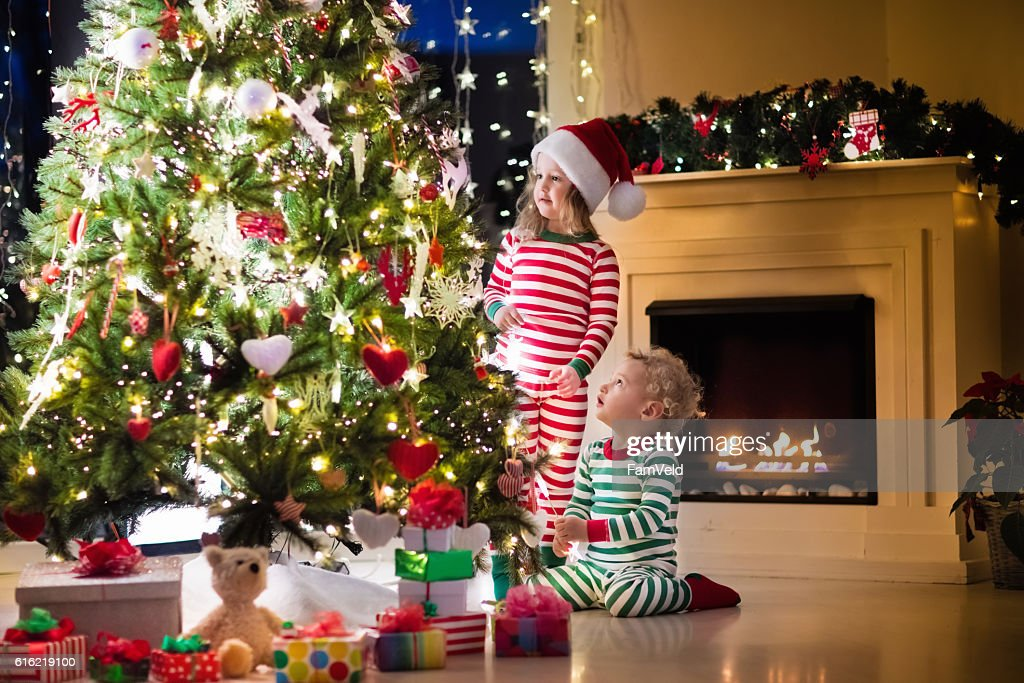 Kids in pajamas under Christmas tree in decorating living room : Stock Photo