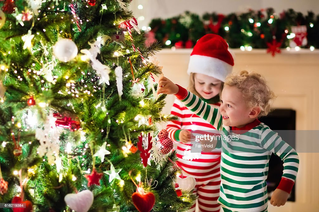 Kids in red and green striped pajamas under Christmas tree : Foto stock