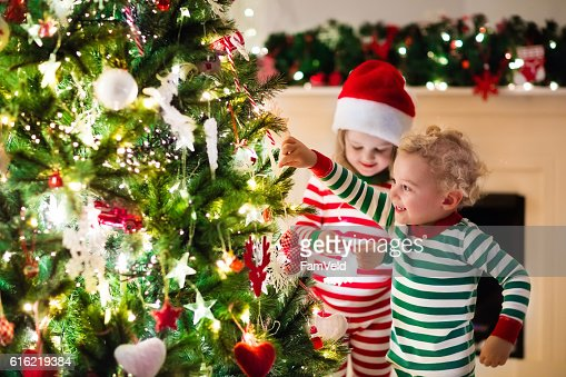 Kids in red and green striped pajamas under Christmas tree : Stock Photo